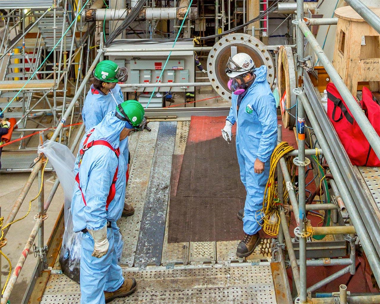 Trois travailleurs portant de l'équipement de sécurité